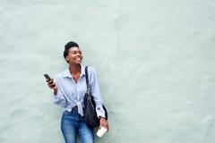 Femme de couleur heureuse tenant le téléphone portable Image stock