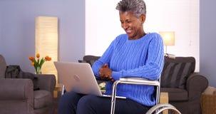 Femme de couleur mûre heureuse s'asseyant dans le fauteuil roulant avec l'ordinateur portable Photographie stock libre de droits
