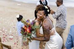 Femme de couleur mariée tenant des fleurs Photographie stock