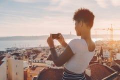 Femme de couleur prenant la photo du paysage urbain sur le téléphone portable Images libres de droits