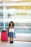 Femme de couleur travaillant avec l'ordinateur portable à l'aéroport attendant aux WI Images libres de droits