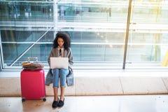 Femme de couleur travaillant avec l'ordinateur portable à l'aéroport attendant aux WI Image stock
