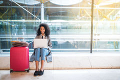 Femme de couleur travaillant avec l'ordinateur portable à l'aéroport attendant aux WI Photos libres de droits