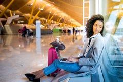 Femme de couleur travaillant avec l'ordinateur portable à l'aéroport attendant aux WI Photographie stock libre de droits