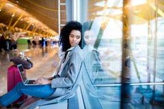 Femme de couleur travaillant avec l'ordinateur portable à l'aéroport attendant aux WI Image libre de droits