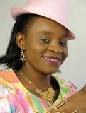 Femme de couleur utilisant un chapeau rose Images libres de droits