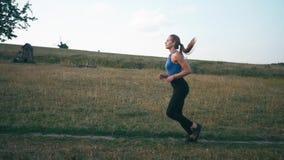 Femme de coureur courant en parc exerçant dehors la technologie portable de traqueur de forme physique Courir au coucher du solei banque de vidéos