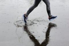 Femme de coureur courant en parc sous la pluie Formation pulsante pour m image libre de droits