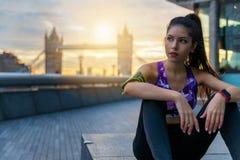 Femme de coureur se reposant après une session de séance d'entraînement à Londres image stock
