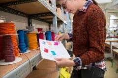 Femme de couture d'habillement choisissant la corde de couleur rouge Images stock