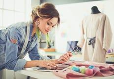 Femme de couturier travaillant avec l'ipad sur elle des conceptions dans le studio image libre de droits