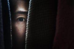 Femme de crainte se cachant dans le cabinet Image libre de droits
