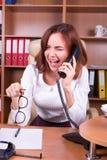 Femme de cri dans le bureau parlant au téléphone Image libre de droits
