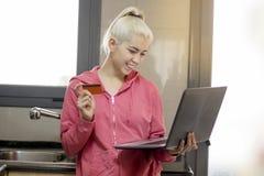 Femme de cuisine sur le PC d'ordinateur portable faisant cuire faisant la nourriture utilisant l'ordinateur FO images stock