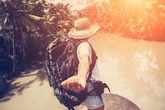Femme de déplacement avec le sac à dos et le chapeau de paille marchant près de la rivière tropicale Photo stock