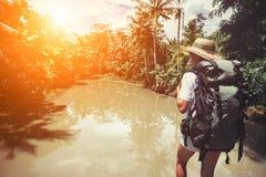 Femme de déplacement avec le sac à dos et le chapeau de paille près de la rivière tropicale Image libre de droits