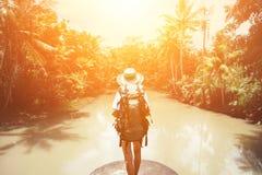 Femme de déplacement avec le sac à dos et le chapeau de paille regardant la rivière tropicale Photos stock