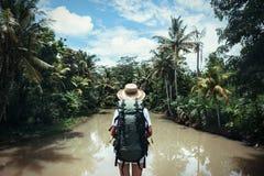Femme de déplacement avec le sac à dos et le chapeau de paille regardant la rivière tropicale le jour ensoleillé Images libres de droits