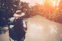 Femme de déplacement avec le sac à dos et le chapeau regardant la rivière tropicale Photos stock