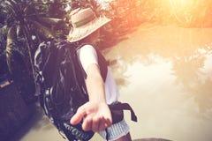 Femme de déplacement Brave avec le sac à dos marchant en avant près de la grande rivière tropicale Photos libres de droits
