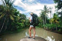 Femme de déplacement Brave avec le sac à dos se tenant sur le bord près de la grande rivière tropicale Image stock