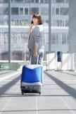 Femme de déplacement d'affaires marchant avec le sac et le téléphone portable Image stock