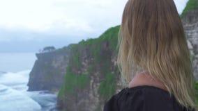 Femme de déplacement sur le fond de vagues de montagne et d'eau de falaise sur le rivage d'océan Montagne de observation de falai banque de vidéos