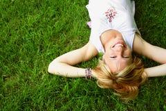 Femme de détente s'étendant sur l'herbe Photographie stock libre de droits