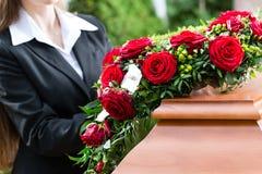 Femme de deuil à l'enterrement avec le cercueil photographie stock libre de droits