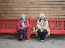 Femme de deux aînés s'asseyant sur un banc rouge dehors Image stock