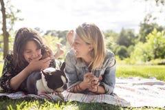 Femme de deux amis avec le chien de terrier dehors au parc Image libre de droits