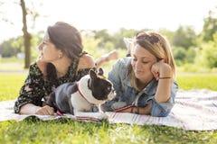 Femme de deux amis avec le chien de terrier dehors au parc Photo libre de droits