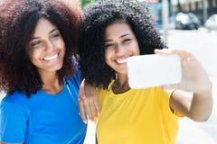 Femme de deux latins prenant le selfie avec le téléphone portable Photos libres de droits