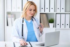 Femme de docteur au travail Portrait du médecin blond de sourire gai à l'aide de la tablette tout en se reposant au bureau photo stock