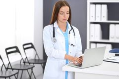 Femme de docteur au travail Portrait du médecin féminin à l'aide de l'ordinateur portable tout en tenant la réception proche à la photos stock