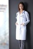 Femme de docteur avec le stéthoscope d'isolement sur le gris images stock