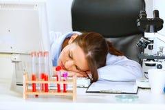 Femme de docteur dormant sur la table de bureau image stock