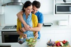 Femme de embrassement d'homme dans la cuisine Photo stock