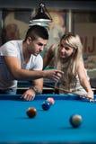 Femme de enseignement d'homme comment jouer la piscine Photographie stock libre de droits