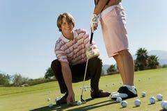 Femme de enseignement d'homme pour jouer au golf Photographie stock libre de droits