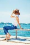 Femme de fille dans des jeans se reposant près de l'eau Image stock