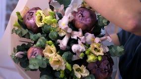 Femme de fleuriste créant et empaquetant le grand bouquet de fleur dans le magasin, plan rapproché de mains banque de vidéos