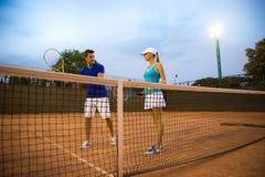 Femme de formation d'homme pour jouer au tennis Image libre de droits