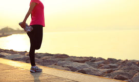 Femme de forme physique étirant des jambes au bord de la mer de lever de soleil Photos libres de droits