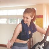 Femme de forme physique avec le pouce pour le succès sur établir dans le gymnase de forme physique photos stock