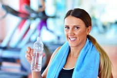 Femme de forme physique Belle jeune fille dans l'eau potable de gymnase, avec la serviette bleue Images libres de droits