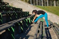 Femme de forme physique de brune faisant l'étirage avant séance d'entraînement au stade Tir extérieur avec des rayons du soleil L photographie stock
