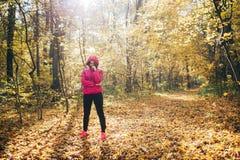 Femme de forme physique courant sur un chemin forestier pendant le lever de soleil Image libre de droits
