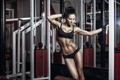 Femme de forme physique dans l'usage noir de sport avec le corps parfait dans le gymnase Image libre de droits