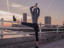 Femme de forme physique dans la pose de yoga sur le pont au lever de soleil Photographie stock libre de droits